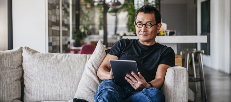 man on couch reading article on tablet
