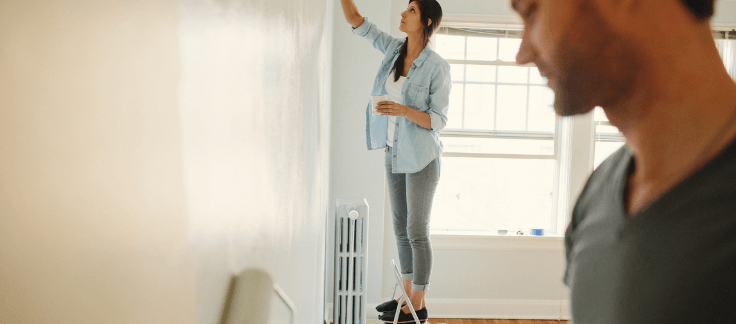 Couple painting the house wall white