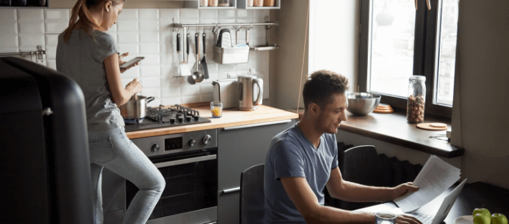 woman cooking and man working on laptop