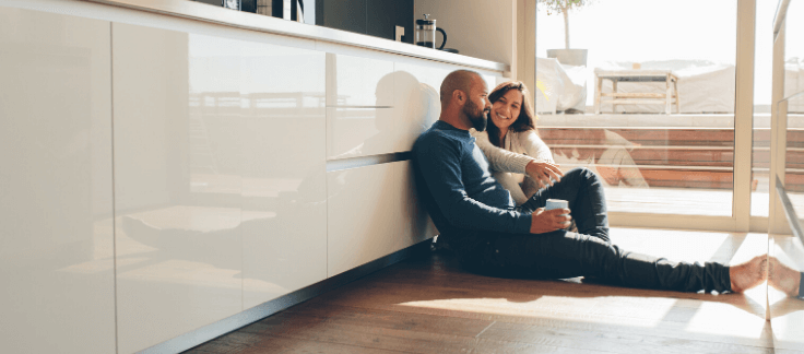 Couple discussing deposit sitting on kitchen floor