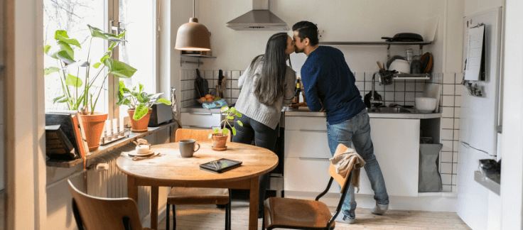 Man and woman in kitchen cooking and kissing