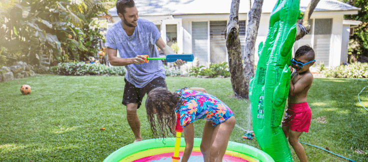 dad having water fight with kids in backyard