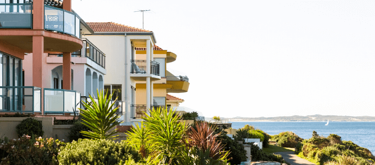 A number of multi-story holiday homes facing outwards to an ocean view