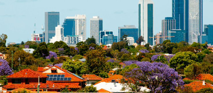 View over suburban rooftops and tree foliage towards a city skyline