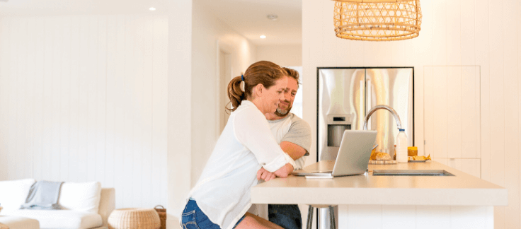 A couple in their kitchen, researching negative gearing on their computer.