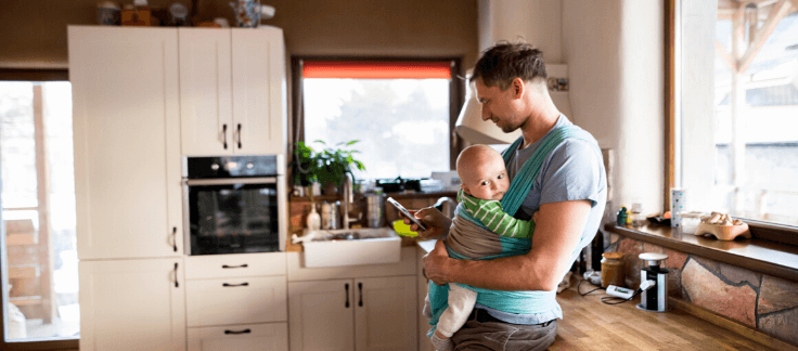 man with baby looking at refinancing on phone