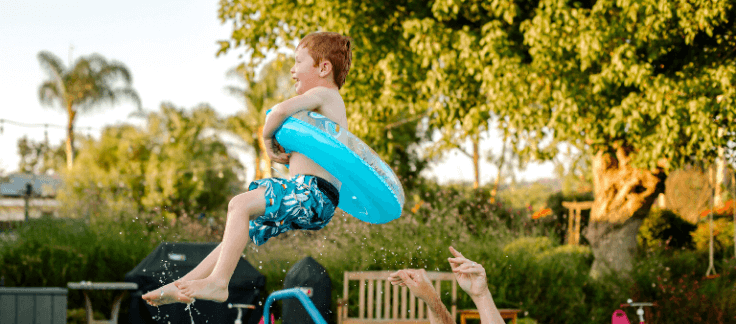 boy flying in air over swimming pool